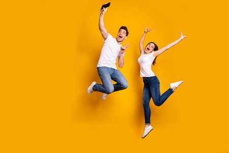 Full length side profile body size photo funky funny crazy people she her he him his guy lady jump high show v-sign make take selfies wear casual jeans denim white t-shirts isolated yellow background