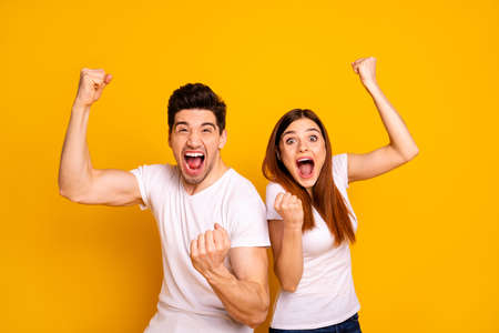Portrait of two nice attractive lovely charming cheerful cheery crazy overjoyed people having fun lottery win winner best lucky victory isolated over vivid shine bright yellow background Imagens
