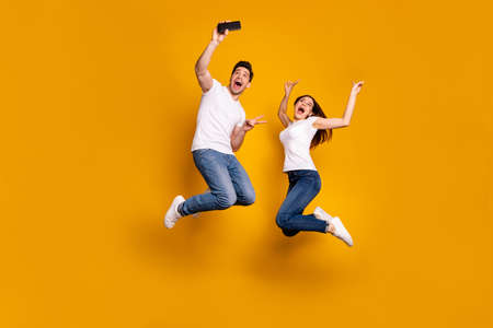 Full length side profile body size photo funky funny two people she her he him his guy lady jump high show v-sign make take selfies wear casual jeans denim white t-shirts isolated yellow background 写真素材 - 122178334