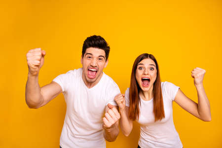 Portrait of two nice attractive lovely charming cheerful cheery ecstatic overjoyed people having fun good mood best lucky attainment isolated over vivid shine bright yellow background 스톡 콘텐츠