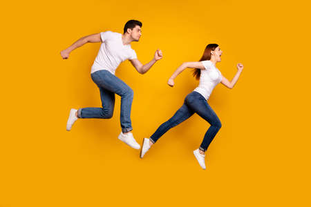 Full length side profile body size photo funky funny she her he him his guy lady jump high hurry shopping black friday low prices wear casual jeans denim white t-shirts isolated yellow background 免版税图像