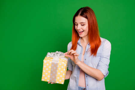 Close up photo beautiful funny funky she her lady arms large big giftbox cant wait more want desire wish eager know what inside wear casual jeans denim shirt isolated green bright background
