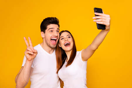 Portrait of his he her she two nice attractive lovely stylish trendy cheerful positive people making taking selfie enjoying showing v-sign isolated over vivid shine bright yellow background