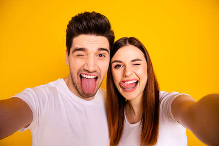 Self-portrait of his he her she two nice attractive cheerful cheery childish comic playful people husband wife showing tongue out having fun isolated over vivid shine bright yellow background