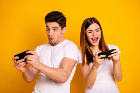 Portrait of his he her she two nice attractive stylish trendy cheerful cheery childish positive people playing app 5g battle contest isolated over vivid shine bright yellow background