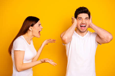 Close up side profile photo two beautiful people she her he him his blame yell fault aggression look up hide ears palms hands arms not listen wear casual white t-shirts isolated yellow background