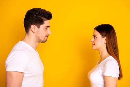Close up side profile photo funny beautiful she her he him his guy lady stand opposite wait first who take eyes off each other lovely look wear casual white t-shirts outfit isolated yellow background