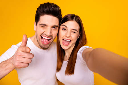 Self-portrait of his he her she two nice attractive lovely charming cute stylish trendy cheerful optimistic people showing thumbup isolated over vivid shine bright yellow background 版權商用圖片