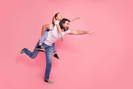Photo de taille de corps de profil latéral pleine longueur elle sa petite dame il lui son papa papa tenir les mains de la petite princesse ferroutage les bras prêts à voler porter des t-shirts blancs décontractés jeans en denim isolé fond rose Banque d'images