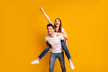 Portrait of his he her she two nice lovely charming attractive playful cheerful cheery dreamy people having fun time isolated over vivid shine bright yellow background