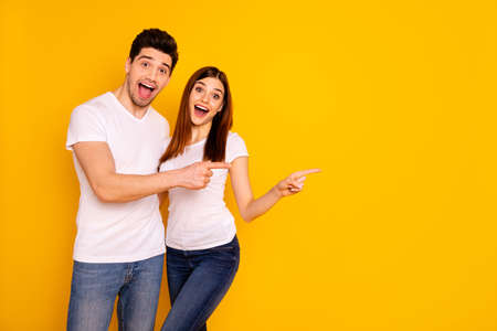 Close up photo beautiful she her he him his pair direct indicate fingers empty space great little low prices shopping shop mall store wear casual jeans denim white t-shirts isolated yellow background