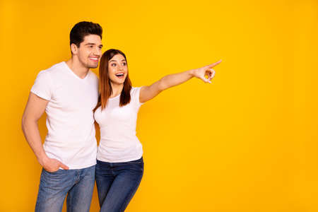 Close up photo beautiful she her he him his pair indicate fingers empty space banner placard sale discount foreign shopping abroad wear casual jeans denim white t-shirts isolated yellow background