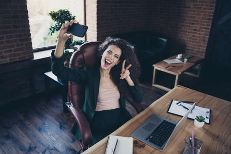 Portrait of trendy charming lady executive have break pause rest relax blog blogging make v-signs feel excited satisfied positive cheerful sit armchair desktop netbook dressed classic jacket in loft Imagens