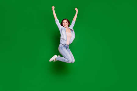 Full length body size view portrait of nice-looking attractive lovely slim fit thin sporty cheerful cheery girl having fun raising hands up isolated over bright vivid shine green background