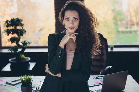 Portrait charming fabulous expert chairman true elegant entrepreneur long wavy curly hairdo touch chin feel dream dreamy satisfied have startup modern loft gadgets dressed fashionable classic jacket Stock Photo