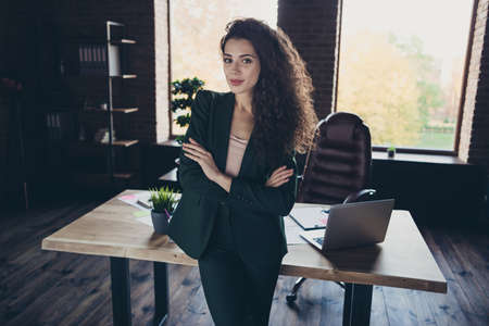 Portrait positive cheerful satisfied entrepreneur content stand desk table computer laptop netbook leather armchair chair furniture dressed modern outfit long wavy curly hair hairstyle company loft