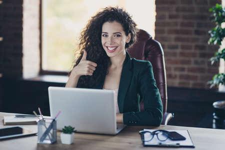 Porträt eines zufriedenen hübschen süßen CEOs klug intelligent mit langen lockigen Haaren machen Werbekonzept Entscheidungsberatung Wahlempfehlung Sitzsessel Holztisch haben modernes Blazer-Gadget industriell Standard-Bild