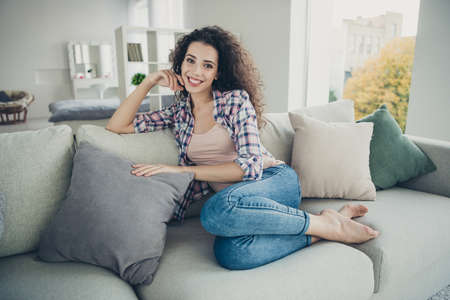Portrait of attractive pretty teen teenager sit divan student glad content have vacation touch pillow wear modern spring trendy checked denim outfit bare foot in living room