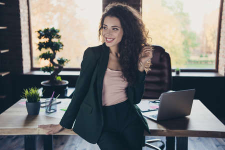 Portrait of real estate manager agent sit desktop satisfied touch long hair feel content glad interested inspired imagine have modern technology leather chair dressed black jacket trousers in interior Stock Photo