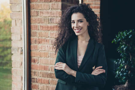 Portrait cute millennial charming freelancer content glad rejoice satisfied enjoy excited relaxed long wavy curly hair hairstyle stand window interior dressed modern stylish trendy classic jacket Stock Photo