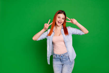 Close up photo beautiful amazing crazy she her foxy lady pretty attractive affectionate adorable show hands arms fingers v-sign say hi wear casual jeans denim shirt isolated green bright background