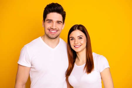 Close up photo funny amazing beautiful couple standing hugging sincere beaming smile easy-going best fellows buddies wear casual white t-shirts outfit isolated yellow background.