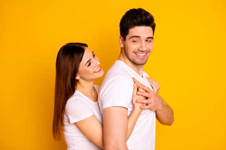 Close up side profile photo beautiful couple hold tight close hands arms husband strong back chest overjoyed emotional wear casual white t-shirts isolated yellow background.