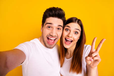 Self-portrait of  two nice attractive lovely trendy cheerful cheery optimistic people husband wife showing v-sign isolated over vivid shine bright yellow background. Stock Photo