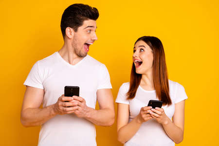 Portrait of  two nice attractive lovely stylish trendy cheerful cheery positive people using new cool gadget  isolated over vivid shine bright yellow background. Imagens
