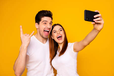 Portrait of two nice attractive adorable cool lovely cheerful cheery positive people making taking selfie enjoying showing horn sign isolated over vivid shine bright yellow background.