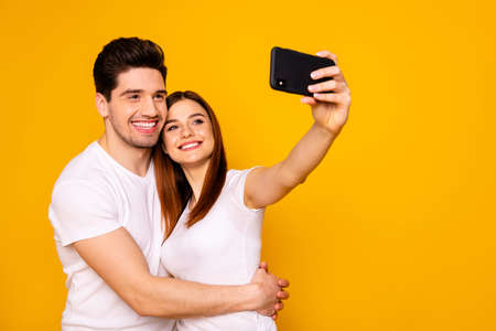 Portrait of  two nice attractive lovely cheerful cheery positive people making taking selfie enjoying free time isolated over vivid shine bright yellow background.