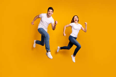 Full length side profile body size photo funky funny couple jump high hurry shopping black friday low prices wear casual jeans denim white t-shirts isolated yellow background.