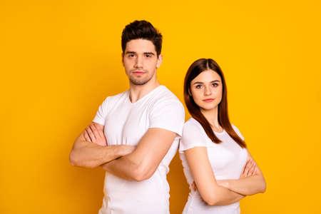 Foto de cerca, profesionales no sonrientes, especialistas en trabajo, trabajadores de trabajo, usan camisetas blancas casuales, fondo amarillo aislado
