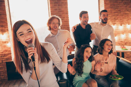 Close up photo best friends buddies karaoke gathering hang out sing she her ladies soloist he him his guys help yell shout scream words song wear dresses shirts formalwear sit sofa loft room indoors