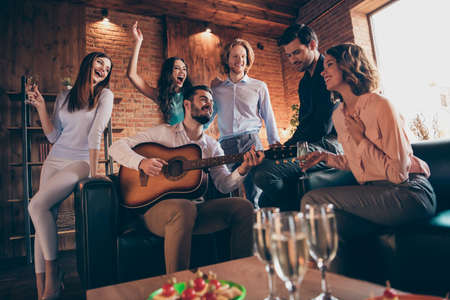 Close up photo serenade gathering best friends hang out vocal soloist play guitar fiance bride surprise romantic she her ladies he him his guys wear dress shirts formal wear sit sofa loft room indoors Stock Photo