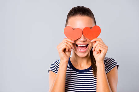Close up photo beautiful amazing she her lady ideal teeth kind hide eyes two red paper hearts shape figure postcards guess who game boyfriend wear blue white striped t-shirt isolated grey background