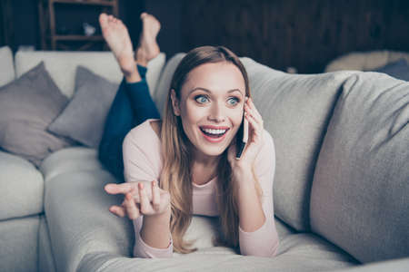 Closeup photo portrait of cheerful positive cute lovely talkative with beaming toothy smile gesturing hands lying down on divan in denim trousers barefoot