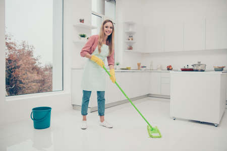 Full length side profile body size photo beautiful busy nice duties she her lady wash white floor carefully not hurry housemaid wear jeans denim casual shirt covered cute apron bright light kitchen