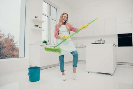 Full length body size photo beautiful nice duties funky she her lady wash white floor pretend rock concert bass guitarist soloist wear jeans denim casual shirt covered cute apron bright light kitchen