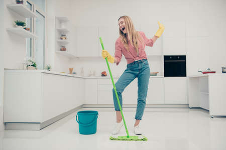 Full length body size photo beautiful amazing funky she her lady wash white floor housemaid karaoke day singing mop crazy movement wear jeans denim casual plaid checkered shirt bright light kitchen Foto de archivo
