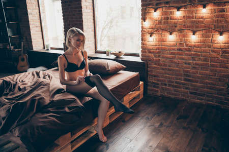 Nice-looking gorgeous attractive winsome luxury elegant slim fit thin feminine lady sitting on bed putting pantyhose off in loft brick industrial style interior room house indoors
