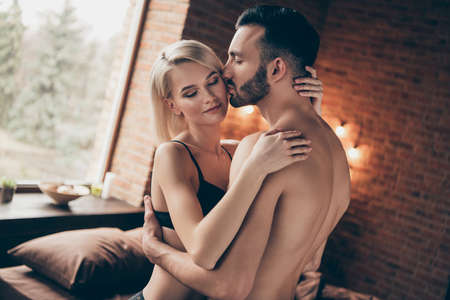 Profile side view portrait of nice charming attractive gorgeous stunning lovely lovable lady cuddling masculine macho guy harmony idyllic affair in loft brick industrial style interior room house