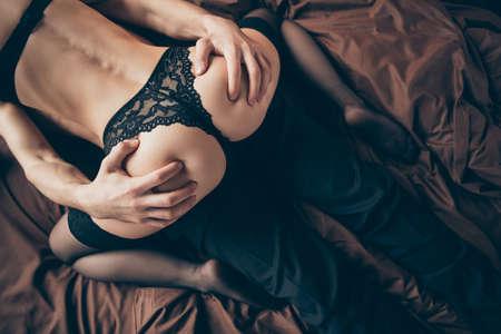 Recadrée en gros plan arrière derrière le haut à angle élevé au-dessus de la photo deux personnes partenaires elle sa dame sur le dessus il lui ses draps couchés désir bras main tenir à peine figure forme boudoir chambre à l'intérieur