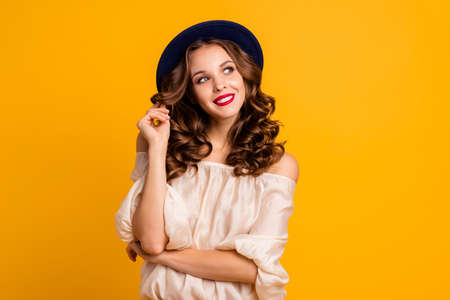 Portrait of her she nice-looking attractive well-groomed winsome lovely pretty cheerful cheery dreamy wavy-haired lady playing with curls isolated over bright vivid shine yellow background