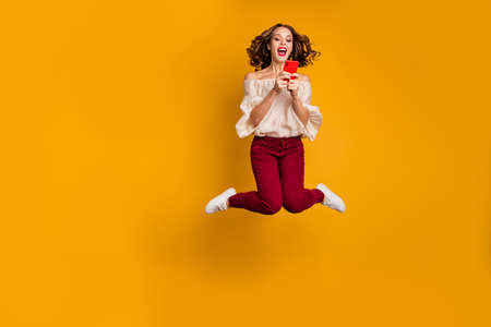Full length body size view portrait of nice attractive slim fit thin glad cheerful cheery wavy-haired lady using modern technology device gadget isolated over bright vivid shine yellow background 写真素材