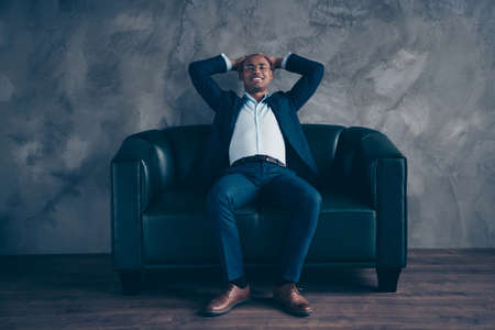 Portrait of his he nice stylish classy elegant attractive cheerful guy professional top company director banker sitting on couch having rest at workplace station gray concrete wall. Banque d'images