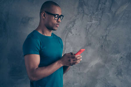 Profile side view portrait of nice lovely attractive good-looking candid guy wearing blue t-shirt using new modern technology device gadget chatting isolated over gray industrial concrete wall.