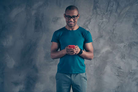 Portrait of his he nice lovely cute attractive good-looking cheerful cheery well-groomed masculine guy wearing blue t-shirt using new device gadget isolated over gray industrial concrete wall.