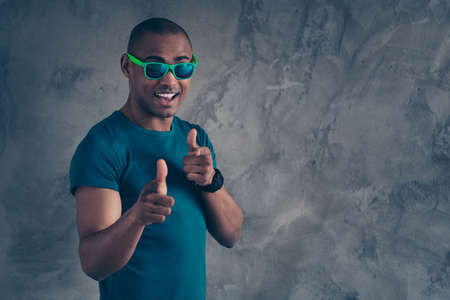 Close up photo amazing funky he him his dark skin macho hot modern look trend hold direct index fingers it is you your turn symbol excited wear specs casual blue t-shirt isolated grey background