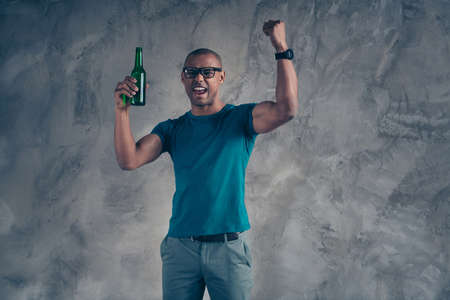 Close up photo amazing yell he him his dark skin macho handsome hand arm hold raise glass ale cider beverage watch football match game wear specs casual blue t-shirt isolated grey background